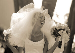 Wedding Photographer Los Angeles at Bel Air Bay Club of bride laughing with bouquet of flowers